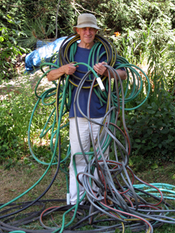 Everything Has A Soul - Two-bit Guru - Image of Dave with hoses - hoses with leaks - gardening - junk and clutter