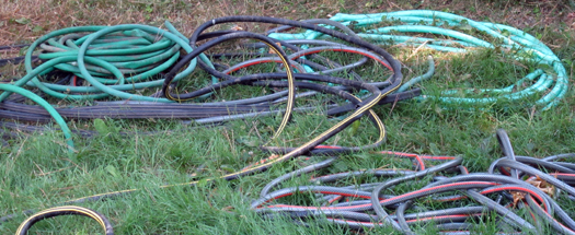 Everything Has A Soul - Two-bit Guru - Image of hoses on grass - hoses with leaks - gardening - junk and clutter