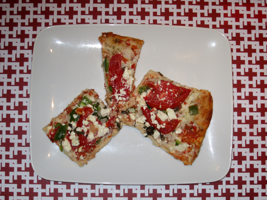Two-bit Guru | Easy Vegetarian Pizza | Photo of cooked frozen pizza on a red and white table cloth. The pizza is topped with onion, tomato, basil, green pepper and feta cheese.