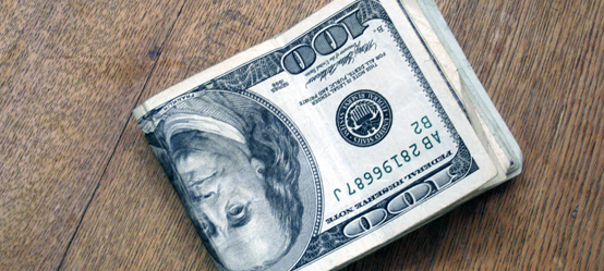 Two-bit Guru | Money & Equality | Photo of a roll of dollar bills.